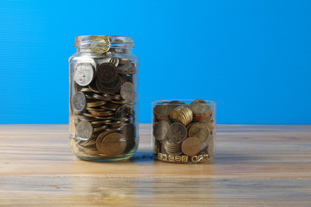 Mason jar with coins over blue back drop. Finance and saving concept. Stock Photo
