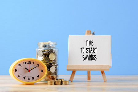 Mason jar with coins and yellow clock over blue back drop.  TIME TO START SAVINGS words. Saving concept.