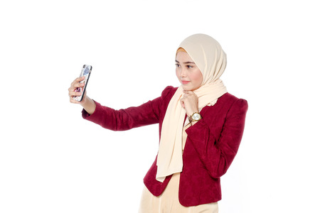 Beautiful young woman taking selfie. Girl photographing herself with phone.