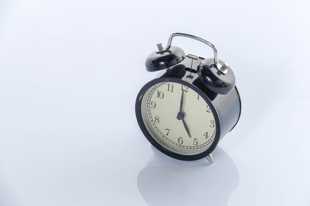 Black alarm clock isolated on white. Stock Photo