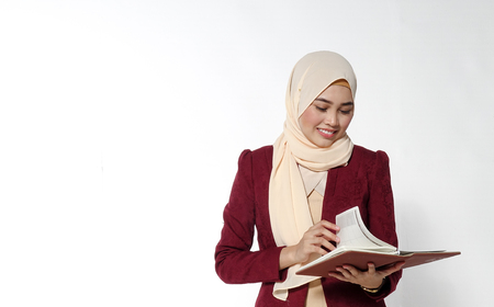 Asian young beautiful executive reading on book with face expression.