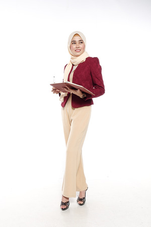 religious clothing: Asian young beautiful executive reading on book with face expression.