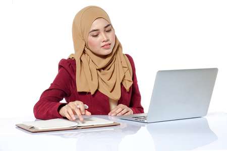 Portrait of pretty Asian hijap woman in front of laptop Stock Photo