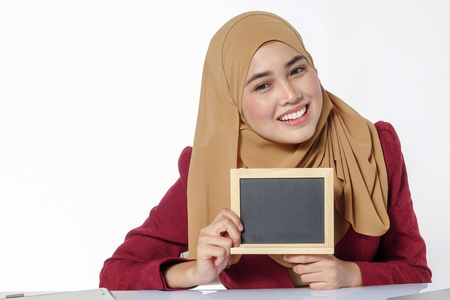 Pretty young Asian lady holds chalkboard.