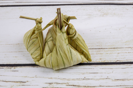 Ketupat (Rice Dumpling) On wooden Background. Ketupat is a natural rice casing made from young coconut leaves for cooking rice during eid Mubarak Stock Photo