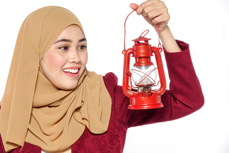 Beautiful woman in a red dress holding a gas lamp