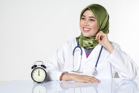 Potrait of stressed young pretty doctor and clock. Overworked concept.