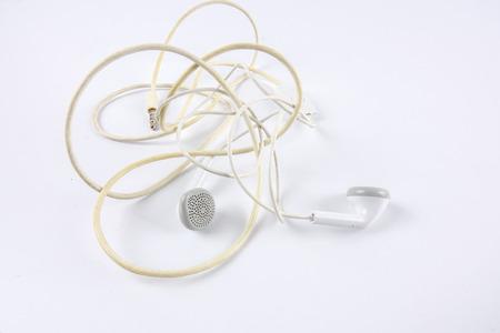 Obselete entangled earphones isolated on white.