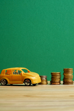 Miniature car on coin stack. Auto trasportation conceptual.