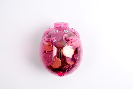 Coins in the red piggy bank isolated on white. Saving and investment conceptual. Stok Fotoğraf