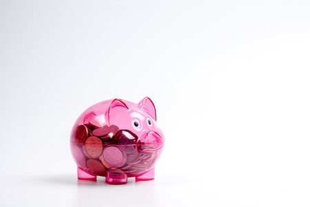 Coins in the red piggy bank isolated on white. Saving and investment conceptual. Stock Photo