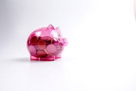 Coins in the red piggy bank isolated on white. Saving and investment conceptual. Archivio Fotografico
