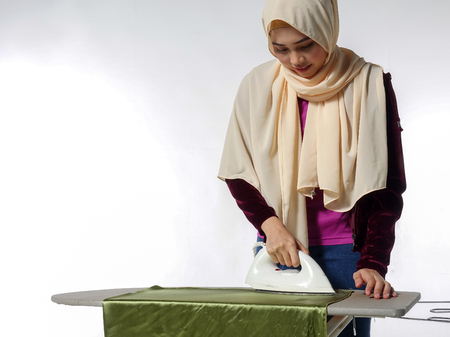 Happy young beautiful woman ironing clothes Stock Photo