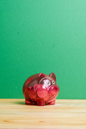 Red piggy bank and jar of coins on green background. Saving and investment concept. Stock Photo