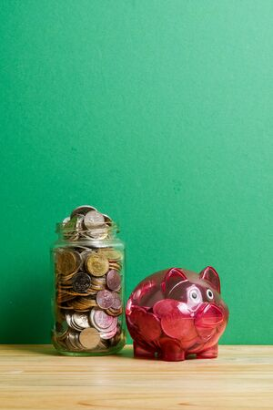 Red piggy bank and jar of coins on green background. Saving and investment concept. Stok Fotoğraf