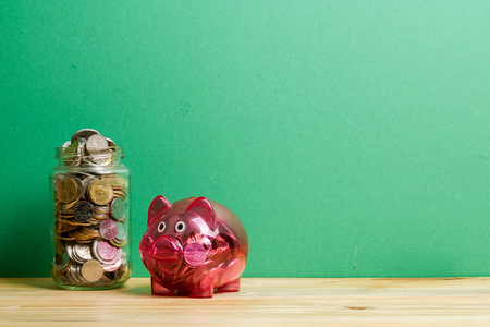 Red piggy bank and jar of coins on green background