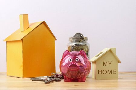 Piggy bank, small house and a bundle of house key. House saving concept