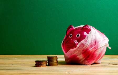 SAVING  DETERIORATE CONCEPT. Red piggy bank with bandage and small stack of coins on the wooden table over green background. Stock Photo