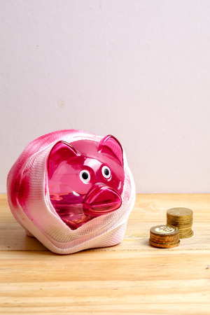 SAVING  DETERIORATE CONCEPT. Red piggy bank with bandage and small stack of coins on the wooden table over white background. Stock Photo