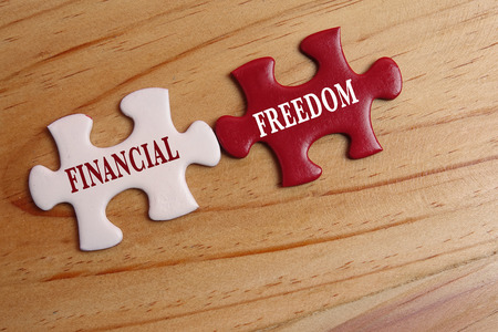 Business concept: White and red jigsaw puzzle with word FINANCIAL FREEDOM.