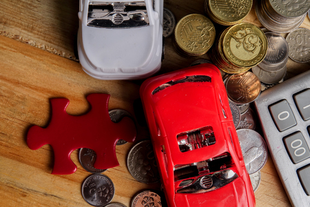 AUTO FINANCING CONCEPT with Small cars, coins, piece of puzzle and calculator on wooden table