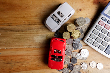 AUTO FINANCING CONCEPT : Small cars,coins,piece of puzzle and calculator on wooden table. Copy Space Stock fotó