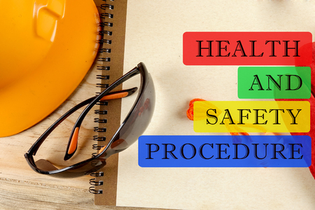 HEALTH AND SAFETY PROCEDURE CONCEPT: Safety hat,glove,glasses,ear plugs and note book. Stock Photo
