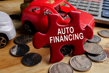 AUTO FINANCING CONCEPT : Small cars,coins,piece of puzzle and calculator on wooden table.
