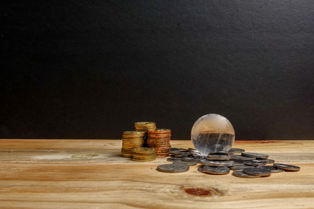 SAVING CONCEPT. Stack of coins on the wooden table over black background. Stock Photo