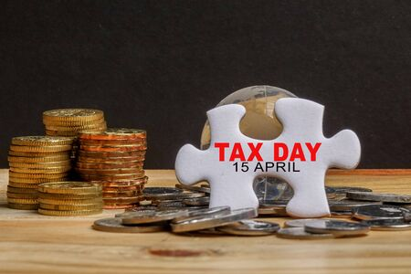 TAX DAY REMINDER CONCEPT. Stack of coins and puzzle with TAX DAY 15 APRIL TEXT on the wooden table over black background. Selective focus
