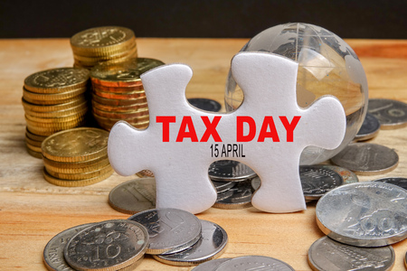 TAX DAY REMINDER CONCEPT. Stack of coins and puzzle with TAX DAY 15 APRIL TEXT on the wooden table over black background.
