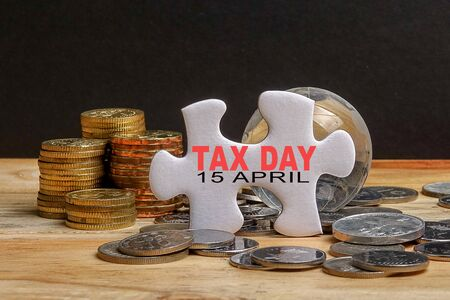 TAX DAY REMINDER CONCEPT. Stack of coins and puzzle with TAX DAY 15 APRIL TEXT on the wooden table over black background. Stock fotó - 94116366