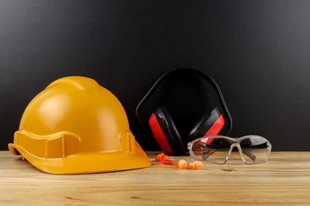 GESUNDHEITS- UND SICHERHEITSKONZEPT. Persönliche Schutzausrüstung auf Holztisch über schwarzem Hintergrund.