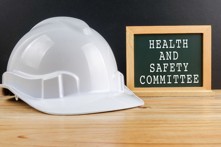 HEALTH AND SAFETY CONCEPT. Personal protective equipment on wooden table over black background with HEALTH AND SAFETY COMMITTEE TEXT Stock Photo