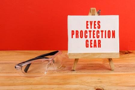 HEALTH AND SAFETY CONCEPT. Personal protective equipment on wooden table over red background.
