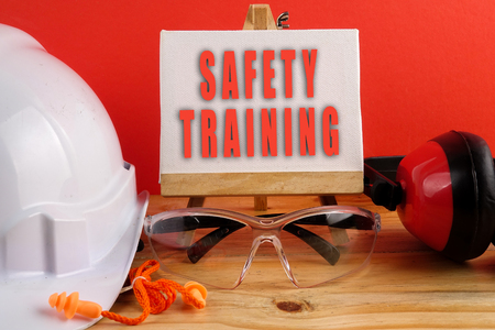 HEALTH AND SAFETY CONCEPT. Personal protective equipment on wooden table over red background WITH SAFETY TRAING TEXT.