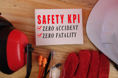 HEALTH AND SAFETY CONCEPT. Personal protective equipment on wooden table background with SAFETY KPI, ZERO ACCIDENT, ZERO FATALITY text.