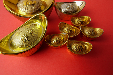 Gold ingots for Chinese New Year festive decorations on a red background. Chinese character means luck,wealth and prosperity as seen in the image.