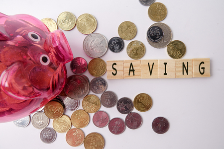 SAVING CONCEPT. Red piggy bank and coins with word SAVING on wooden plates.