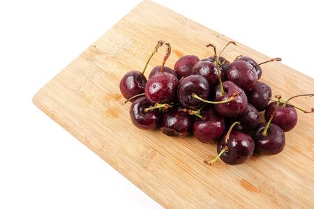Sweet red cherries on a wooden background.