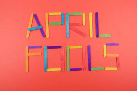 April Fools  background with colourful sticks on red background