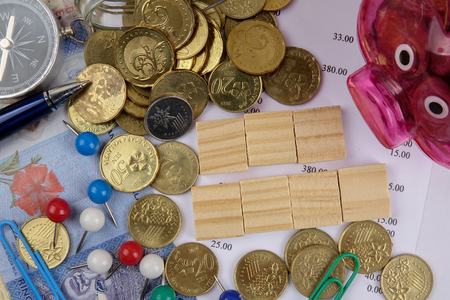 TAX CONCEPT. Coins,calculator,bank notes and wood plate on a white table.