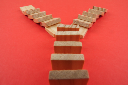 Domino effect isolated on red background. Selective focus