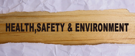 HEALTH, SAFETY AND ENVIRONMENT CONCEPT text at plain torn paper.
