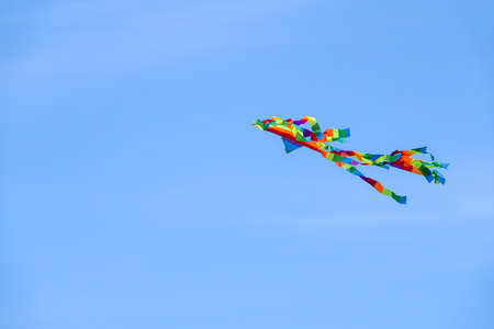 Colourful kite over  the blue sky. Stock Photo