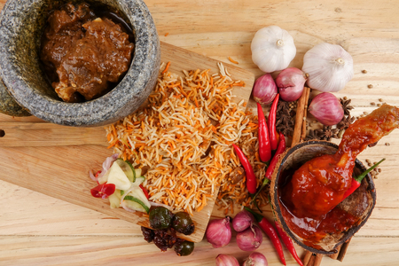 Nasi Briyani is a wholesome rice-based dish prepared with spices, rice, meat and vegetables. Imagens