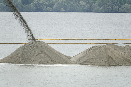 Dredging panning sand on the beach during the construction of a new sea freight terminal in the harbor of port.