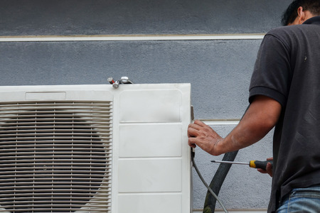 Unidentified Young Asian Man repairing the  Air Conditioning System Stock Photo