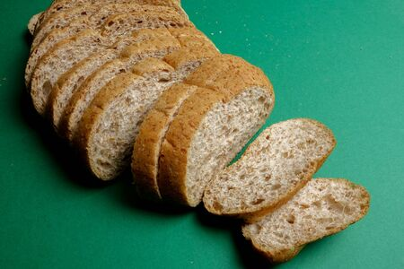 A loaf of wholegrain bread on a green background