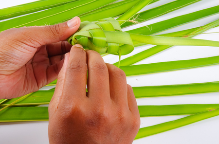 Making of Ketupat, a natural rice casing made from young coconut leaves for cooking rice Stock Photo